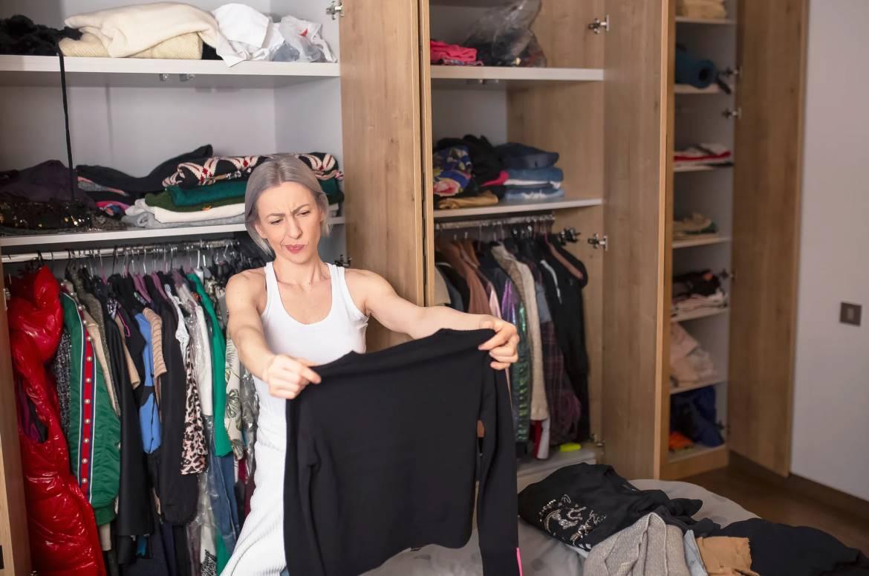 Donna che sceglie abiti per decluttering