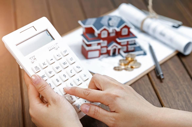 Donna con calcolatrice che calcola il valore della sua casa